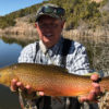 fly fisherman holding colorful tiger trout
