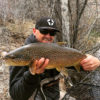 Fly fisherman with trophy brown trout